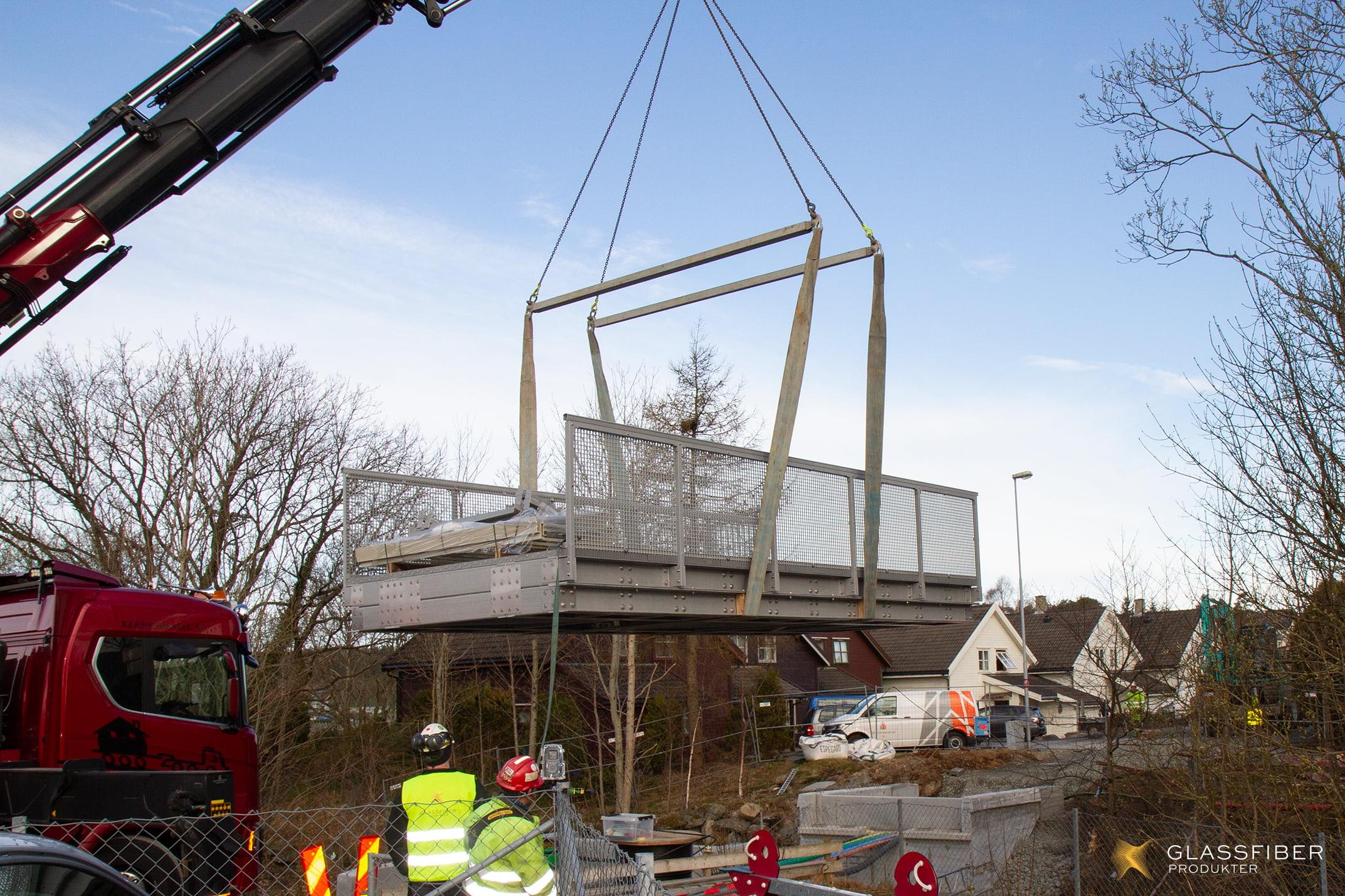 Broen blir løftet av kranbilen og heiset på plass